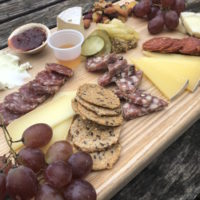 Cheese board with sheep cheese, charcuterie and grapes by Green Dirt Farm