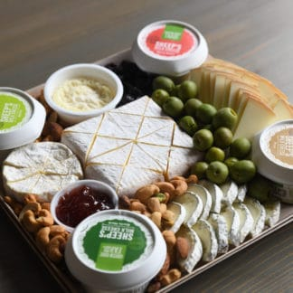 Sheep cheese board by Green Dirt Farm complete with grapes and nuts.